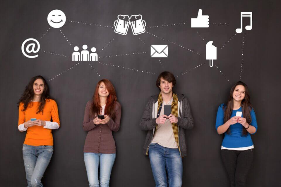 Four people texting in front of a blackboard in social media concept.