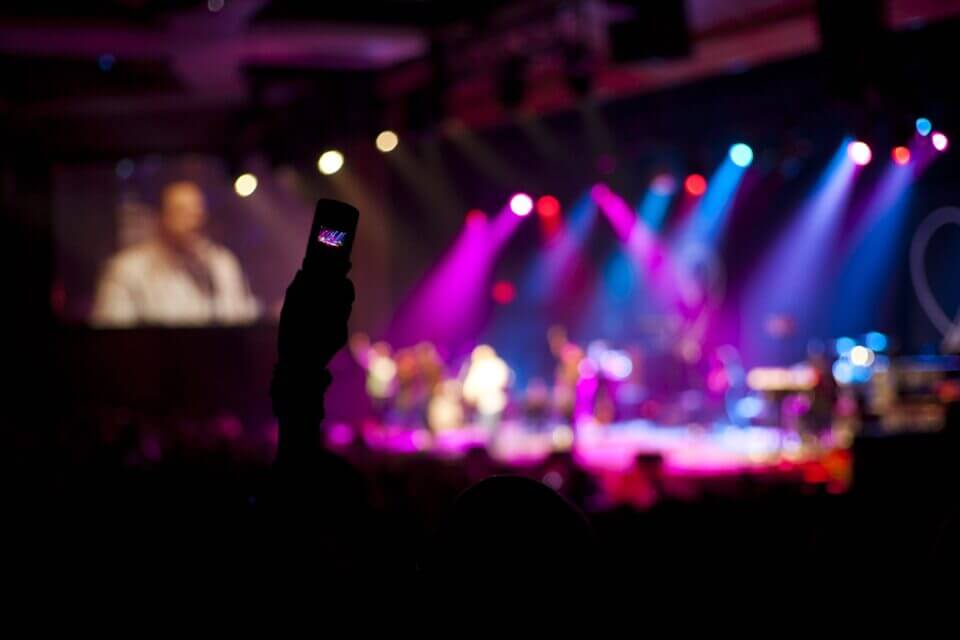 During a worship concert. Intentionally blurred image. Great for backdrop.Silhouette hand of an anonymous person taking pictures with cell phone camera.
